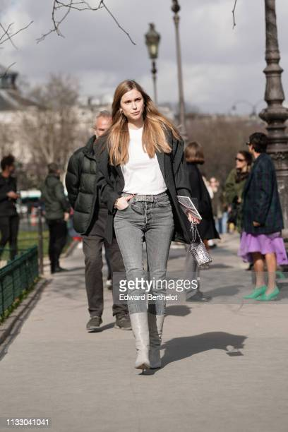 Pernille Teisbaek wears a white top a grey oversize jacket a glittering strass belt grey stonewashed jeans a shiny metal mesh bag grey pointy...