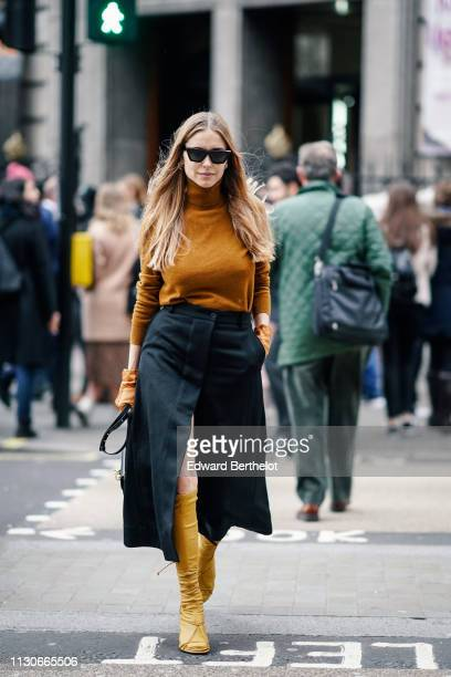 Pernille Teisbaek wears an orange wool turtleneck pullover a black skirt yellow boots during London Fashion Week February 2019 on February 18 2019 in...
