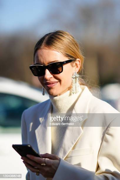 Pernille Teisbaek wears Chanel sunglasses, earrings, rings, a fluffy cream-color turtleneck, a white jacket, outside Chanel, during Paris Fashion...