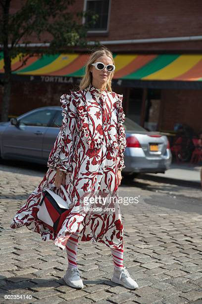 Pernille Teisbaek wears oversized Acne Studios white sunglasses a white Ellery dress with red flowers red Loewe bag and white Adidas sneakers outside...