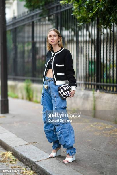Pernille Teisbaek wears silver pearls earrings from Chanel, black crop-top, a black with white borders Chanel cardigan, a black and white checkered...