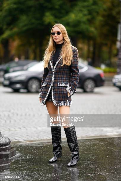 Pernille Teisbaek wears sunglasses a black turtleneck black leather shorts a white trimmed brown and grey plaid jacket black crocodile pattern...