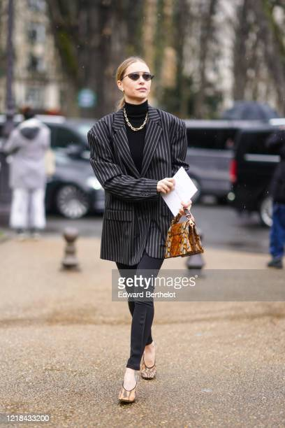 Pernille Teisbaek wears sunglasses, a black turtleneck pullover, a golden chain necklace, a gray striped oversized blazer jacket, a brown snake...