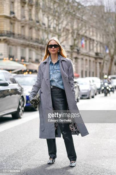 Pernille Teisbaek wears sunglasses, a blue denim shirt, a black and white houndstooth pattern printed long coat with floral print inner lining, a...