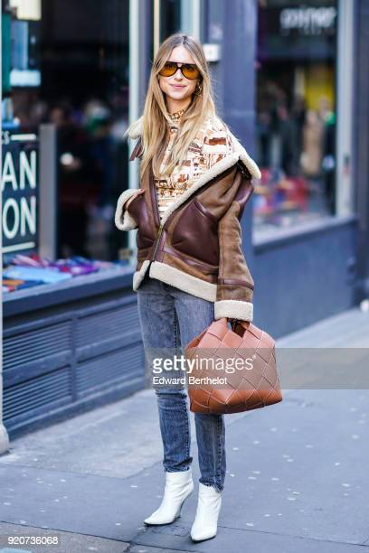 Pernille Teisbaek wears sunglasses a brown aviator jacket a brown bag blue jeans white shoes during London Fashion Week February 2018 on February 17...