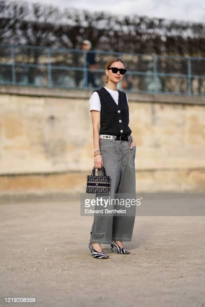 Pernille Teisbaek wears sunglasses, a white t-shirt, a navy blue vest, a mini Dior shopping bag, a belt, gray pants, black and white zebra print...