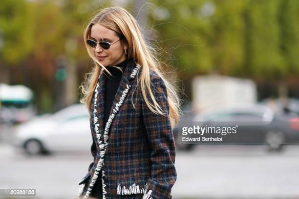 Pernille Teisbaek wears sunglasses, earrings, a black turtleneck, a white trimmed brown and grey plaid jacket, outside Chanel, during Paris Fashion...