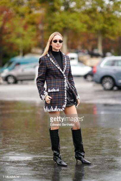 Pernille Teisbaek wears sunglasses, earrings, a black turtleneck, black leather shorts, a white trimmed brown and grey plaid jacket, black crocodile...