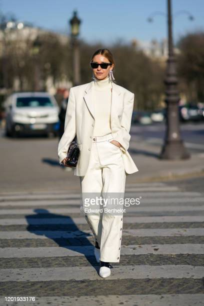 Pernille Teisbaek wears sunglasses earrings a white turtleneck pullover an oversized blazer jacket a Chanel quilted bag flare pants pointy shoes...