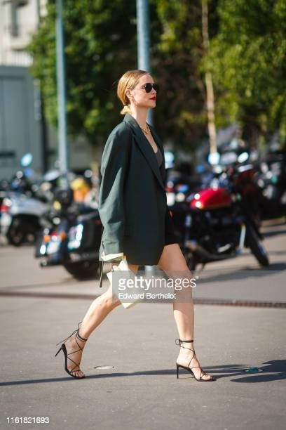 Pernille Teisbaek wears sunglasses earrings necklaces a khaki top a darkgreen oversized jacket black shorts a pale yellow bucket bag black gladiator...