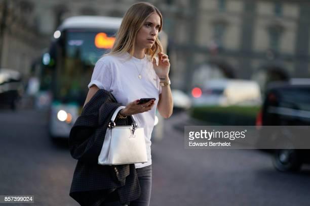 Pernille Teisbaekwears a white tshirt a white bag boots gray pants outside Louis Vuitton during Paris Fashion Week Womenswear Spring/Summer 2018 on...