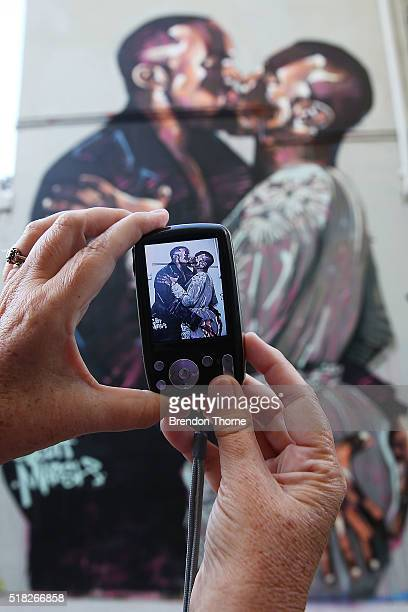Peron takes a photo of a mural by artist Scott Marsh is seen on Teggs Lane, Chippendale on March 31, 2016 in Sydney, Australia. The artist and the...