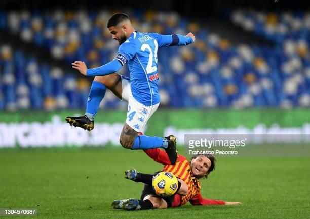 Perparim Hetemaj of Benevento Calcio tackles Lorenzo Insigne of Napoli during the Serie A match between SSC Napoli and Benevento Calcio at Stadio...