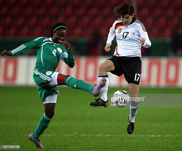Perpetua Nkwocha of Nigeria challenges Ariane Hingst of Germany during the women's international friendly match between Germnay and Nigeria at...