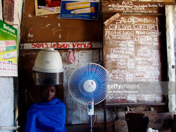 Perpeture Tulubeli gets her hair done in a hair saloon in a wooden shack on February 28 2002 in central Kinshasa Congo She wants to look nice and...