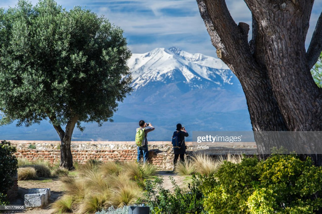 Perpignan (southern France). The snow-covered Canigou mountain viewed from the terraces of the Palace of the Kings of Majorca (Palau dels Reis de Mallorca in Catalan). Tourists taking pictures.