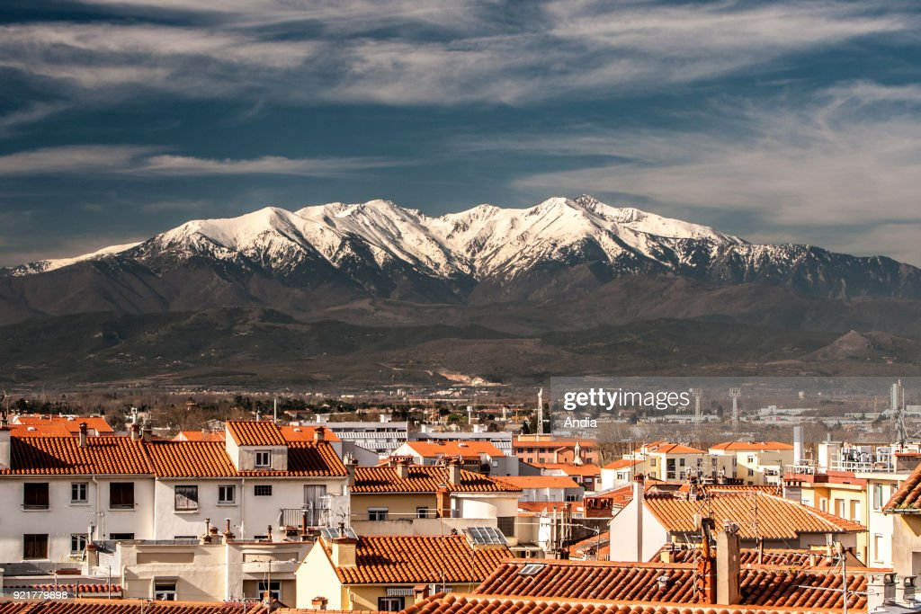 Perpignan (southern France). Tiled roofs of the popular district of Saint-Mathieu, with the snow-covered Canigou mountain viewed from the terraces of the Palace of the Kings of Majorca (Palau dels Reis de Mallorca in Catalan).