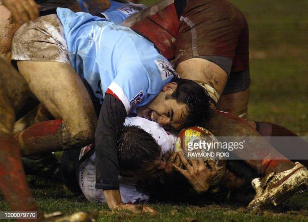 Perpignan's fly-half jean-Philippe Grandclaude vies with Biarritz's players during their French Top 14 Rugby Union match, 28 January 2006 in...