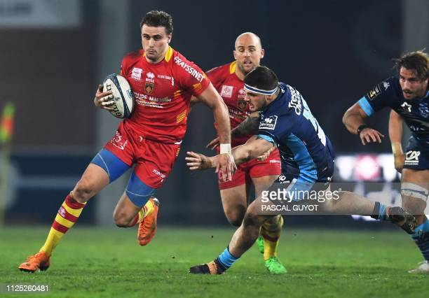 Perpignan's French wing Jean-Bernard Pujol vies with Montpellier's French lock Julien Ledevedec during the French Top 14 rugby union match between...