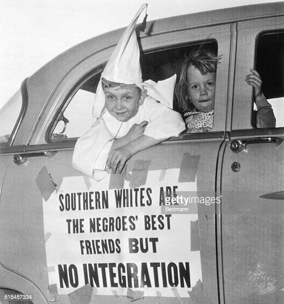 Perry Blevens is all dressed up in his Ku Klux Klansman robes as he rides in the motorcade staged here by the Klan, April 14th. Looking out the car...