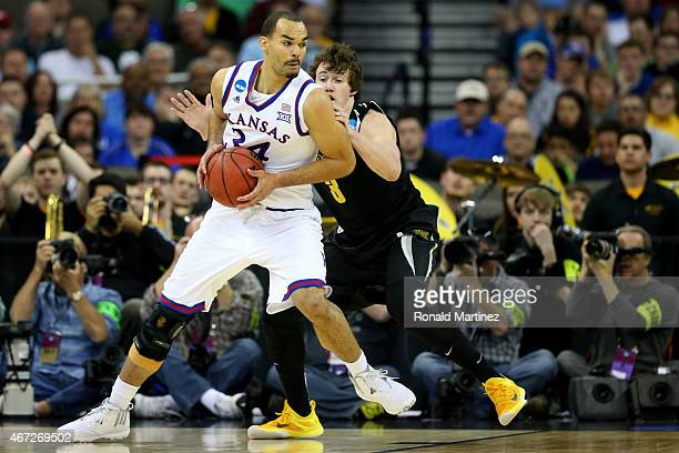 Perry Ellis of the Kansas Jayhawks dribbles past Evan Wessel of the Wichita State Shockers in the first haf during the third round of the 2015 NCAA...