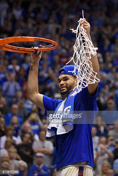 Perry Ellis of the Kansas Jayhawks holds up the net as he and members of his team celebrate winning the Big 12 Conference Championship at Allen...