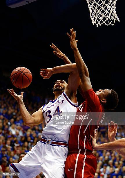 Perry Ellis of the Kansas Jayhawks shoots as Dante Buford of the Oklahoma Sooners defends during the game at Allen Fieldhouse on January 4 2016 in...
