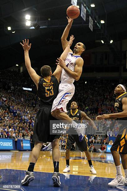 Perry Ellis of the Kansas Jayhawks shoots over Nathan Boothe of the Toledo Rockets at Allen Fieldhouse on December 30 2013 in Lawrence Kansas