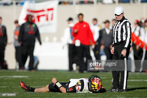 Perry Hills of the Maryland Terrapins lays on the field after being knocked down while passing against the Michigan State Spartans during the game at...