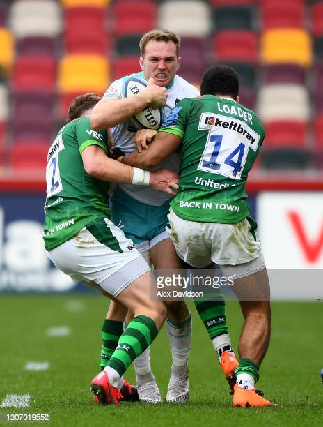 Perry Humphreys of Worcester Warriors is tackled by Theo Brophy Clews and Ben Loader of London Irish during the Gallagher Premiership Rugby match...