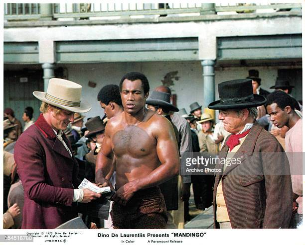 Perry King reads a letter next to Ken Norton in a scene from the film 'Mandingo' 1975