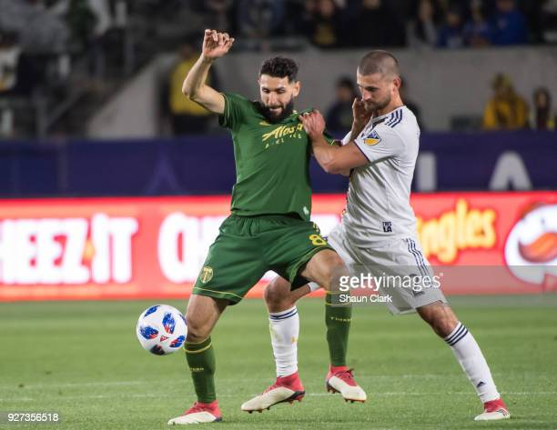 Perry Kitchen of Los Angeles Galaxy battles Diego Valeri of Portland Timbers during the Los Angeles Galaxy's MLS match against Portland Timbers at...