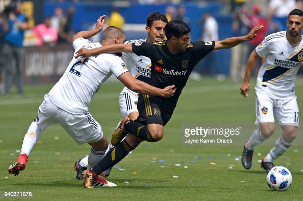 Perry Kitchen of Los Angeles Galaxy defends Carlos Vela of Los Angeles FC as they chase down the ball in the first half of the game at StubHub Center...