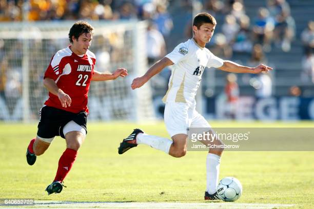 Perry Kitchen of the University of Akron races past Dylan Mares of the University of Louisville during the Division I Men's Soccer Championship held...