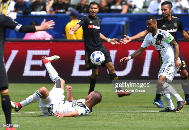 Perry Kitchen passes the ball to Ashley Cole of Los Angeles Galaxy after being knocked to the ground in the second half of the game against the Los...
