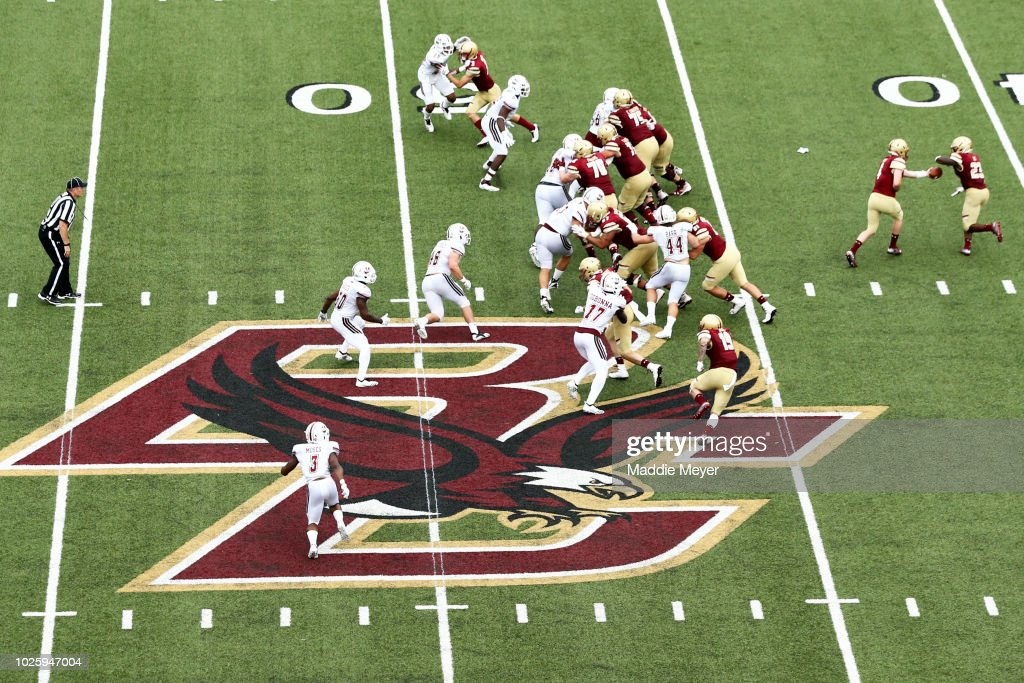 EJ Perry #4 of the Boston College Eagles hands the ball off to Travis Levy #23 during the game against the Massachusetts Minutemen at Alumni Stadium on September 1, 2018 in Chestnut Hill, Massachusetts.