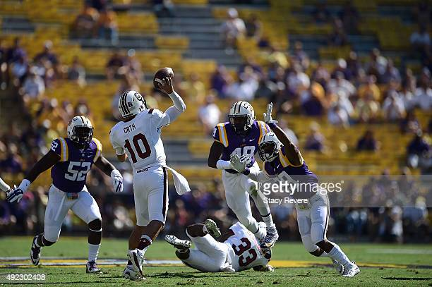 Perry Orth of the South Carolina Gamecocks is pressured by Kendell Beckwith Arden Key and Rickey Jefferson of the LSU Tigers during a game at Tiger...