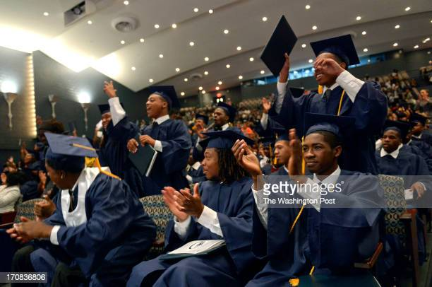 Perry Street Prep rugby player Christian Adams seated center claps as his class is announced as graduates at Howard University's Cramton Auditorium...