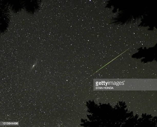 A Perseid meteor is seen near the Andromeda Galaxy over Rocky Mountain National Park in Colorado in the early morning hours of August 12 2018 The...