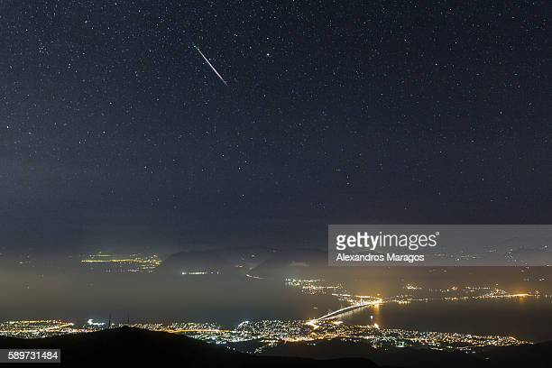a perseid meteor over the rio-antirio bridge in patras, greece - stella cometa foto e immagini stock