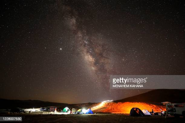 Perseid meteor streaks across the sky above a camping site at the Negev desert near the city of Mitzpe Ramon on August 11, 2020 during the Perseids...