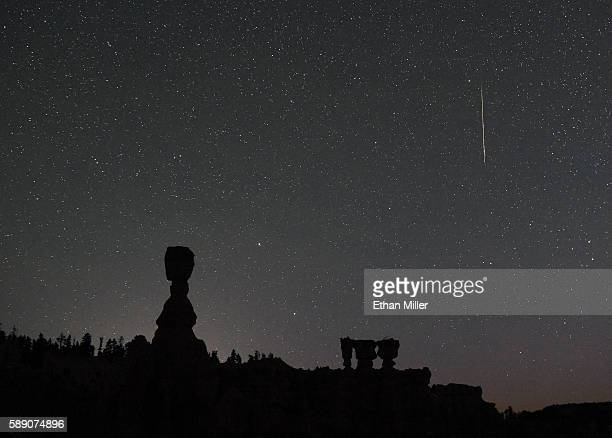 Perseid meteor streaks across the sky above the hoodoos named Thor's Hammer and the Three Sisters early on August 13 2016 in Bryce Canyon National...