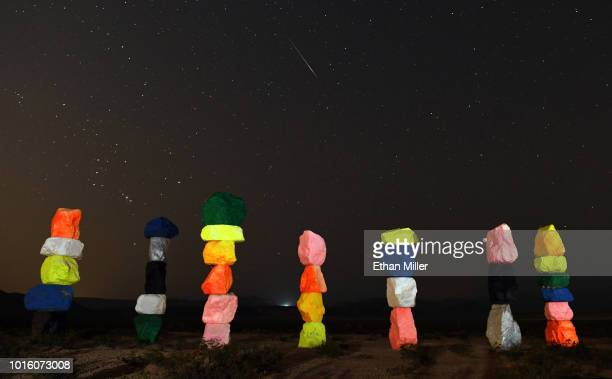 Perseid meteor streaks across the sky above the 'Seven Magic Mountains' art installation early on August 13 2018 near Jean Nevada The annual display...