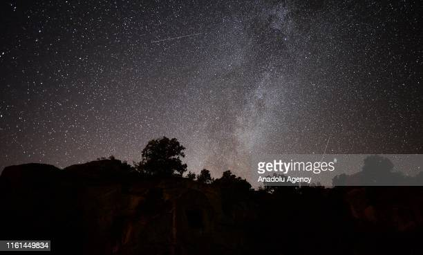 Perseid meteors streak across the night sky over the ancient city of Mesotimolos in Esme district of Turkey's western Usak province on August 13,...