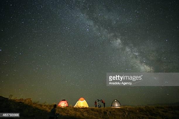 Perseid meteors streak across the sky during the annual Perseid meteor shower in Edremit district of Van eastern Turkey on August 12 2015 The display...