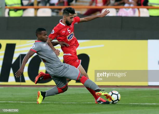 Persepolis' Bashar Rasen vies for the ball against alDuhail's Almoez Ali during the AFC Champions League quarter final match between Persepolis FC...