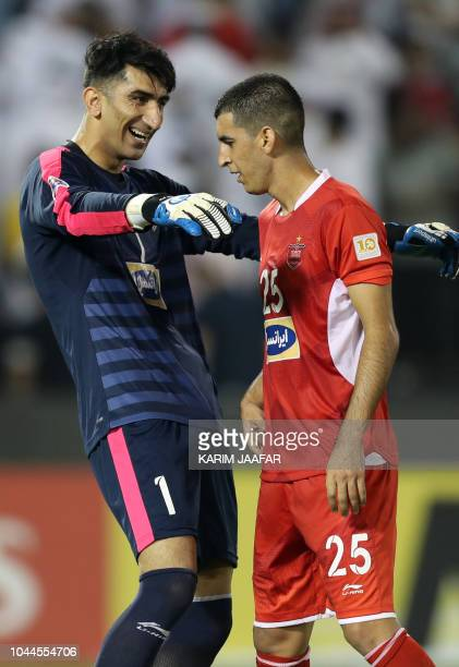 Persepolis FC's Alireza Beiranvand celebrates with teammate Ehsan Alvanzadeh during the AFC Champions League semifinal first leg match between AlSadd...