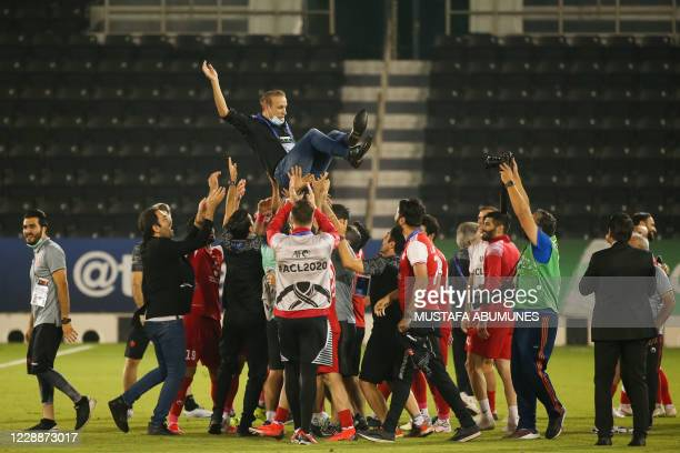 Persepolis' players throw their coach in the air to celebrate their win during the AFC Champions League semi-finals match between Saudi's Al-Nassr...