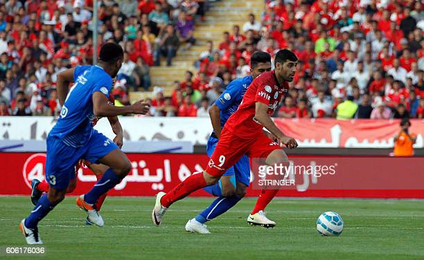 Persepolis's Mehdi Taremi runs past Esteghlal players during their Persian Gulf Pro League derby football match between Persepolis FC and Esteghlal...