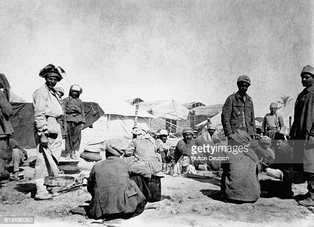 Persian Arab and Kurd prisoners gather around a cookhouse at a Mesopotamian prison camp in April 1916 France and Britain divided the Middle East into...